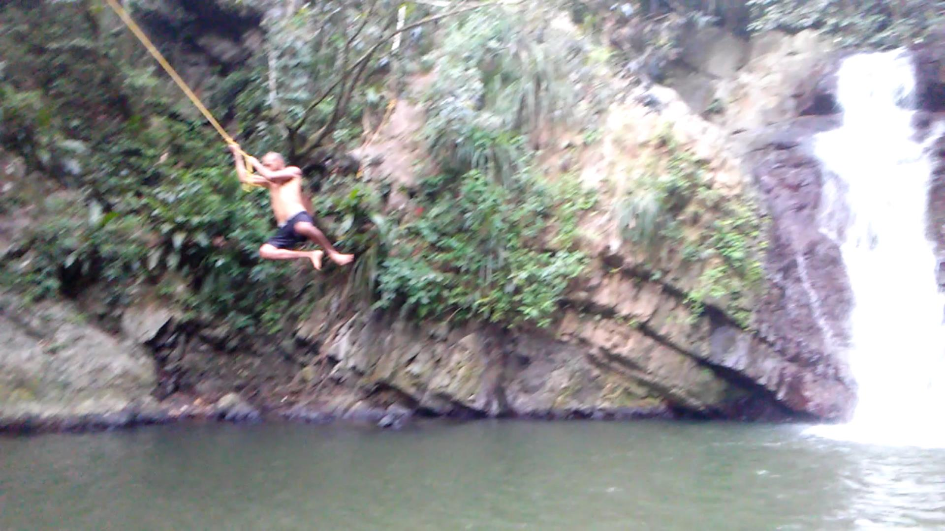 jumping from a rope in a beautiful river in puerto rico